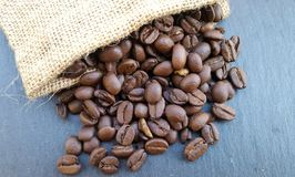 Granos de café en un bolso en fondo de piedra oscuro Imagenes de archivo