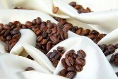 Granos de café en un concepto de seda amarillento lujoso Imagen de archivo