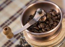 Granos de café en un molino de cobre foto de archivo libre de regalías