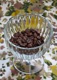 Granos de café en un plato de cristal en un backgroun floral Fotos de archivo libres de regalías