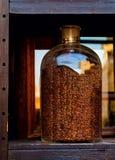 Granos de café en un tarro de cristal grande en el fondo de la ventana, primer, fotos de archivo