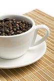 Granos de café en un tazón de fuente blanco Imagenes de archivo