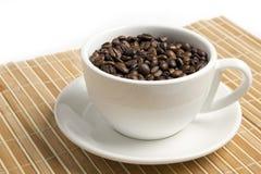 Granos de café en un tazón de fuente blanco Fotos de archivo libres de regalías