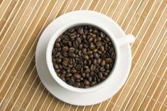 Granos de café en un tazón de fuente blanco Imágenes de archivo libres de regalías