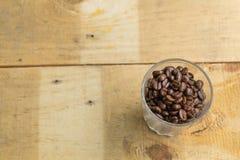 Granos de café en un vidrio en la madera Foto de archivo libre de regalías