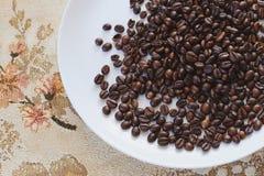 Granos de café en una placa blanca Fotografía de archivo