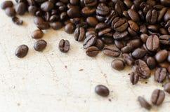Granos de café en una tabla de madera Imagenes de archivo