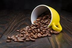 Granos de café en una taza amarilla Imagen de archivo