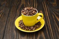 Granos de café en una taza amarilla Imágenes de archivo libres de regalías