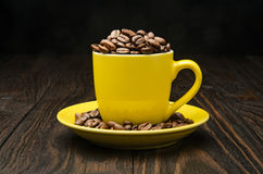 Granos de café en una taza amarilla Fotos de archivo libres de regalías