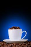 Granos de café en una taza blanca en un fondo azul Imagenes de archivo