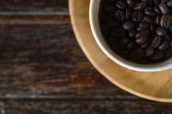 Granos de café en una taza en fondo de madera Imágenes de archivo libres de regalías