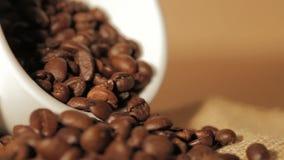 Granos de café en una taza en la tabla de madera metrajes