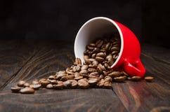 Granos de café en una taza roja Imágenes de archivo libres de regalías