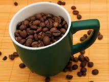 Granos de café en una taza verde Imagen de archivo libre de regalías