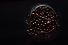 Granos de café en vidrio en negro Imágenes de archivo libres de regalías