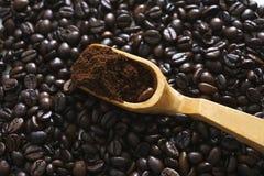 Granos de café fragantes y espátula de madera foto de archivo