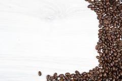 Granos de café frescos en una tabla texturizada de madera Fotos de archivo libres de regalías