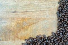 Granos de café frescos en una tabla texturizada de madera Imagen de archivo