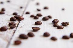 Granos de café fritos en la falta de definición parcial de los tableros blancos Foto de archivo libre de regalías