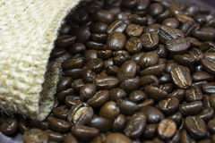 Granos de café fuera de su bolso II del yute Foto de archivo libre de regalías