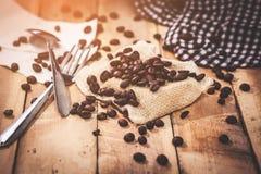 Granos de café de la historia por la mañana en el fondo de madera Imagen de archivo