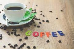 Granos de café de la historia y taza del café con leche por la mañana en la madera b Imagen de archivo
