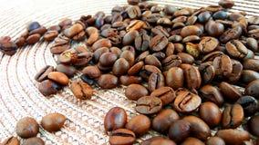 Granos de café marrones asados en fondo ligero del paño foto de archivo libre de regalías