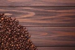Granos de café naturales en fondo de madera marrón foto de archivo