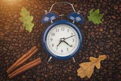 Granos de café, palillos de canela y despertador asados Mujer joven en cama en la mañana Buenos días Humor del otoño Fondo, opini fotos de archivo