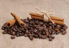 Granos de café, palillos de canela en la arpillera Fotografía de archivo libre de regalías