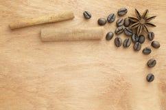 Granos de café, palillos de canela y anís en una tabla de madera fotografía de archivo libre de regalías