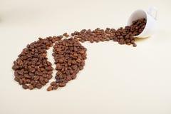 Granos de café que caen de la taza blanca fotos de archivo