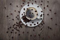 granos de café que circundan sobre la taza de café Foto de archivo libre de regalías