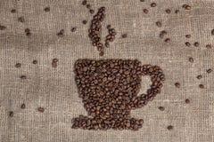 Granos de café que forman la taza en la arpillera imagenes de archivo