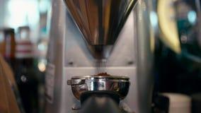 Granos de café que muelen con la amoladora profesional Machine Coffee Maker en café metrajes