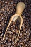 Granos de café que se derraman fuera de la cucharada de madera Foto de archivo