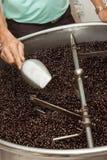 Granos de café recientemente asados en un tostador de café Foto de archivo