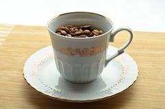 Granos de café secados en una taza Foto de archivo