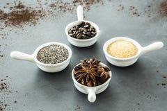 Granos de café, semillas y anís de estrella en cuencos pequeños, a juego en a imagen de archivo libre de regalías