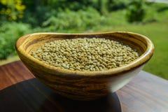 Granos de café sin tostar verdes en un cuenco de bambú Fotos de archivo