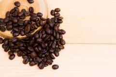 Granos de café sobre la placa de madera Foto de archivo libre de regalías