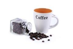 Granos de café, taza y un envase de cristal Fotos de archivo libres de regalías