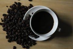 Granos de café, tazas del café con leche colocadas en de madera Imagenes de archivo