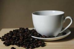 Granos de café, tazas del café con leche colocadas en de madera Foto de archivo