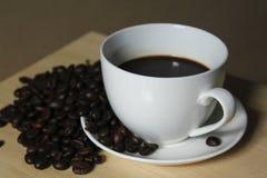 Granos de café, tazas del café con leche colocadas en de madera Fotos de archivo libres de regalías