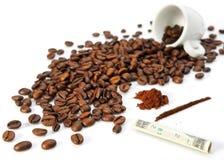 Granos de café, una taza y billete torcido Imagen de archivo libre de regalías