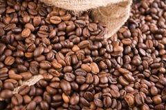 Granos de café vertidos fuera de un saco abajo foto de archivo libre de regalías
