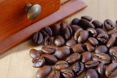 Granos de café y amoladora de café en la tabla imagenes de archivo