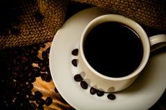 Granos de café y café en la taza blanca en la tabla de madera con arpillera Imágenes de archivo libres de regalías